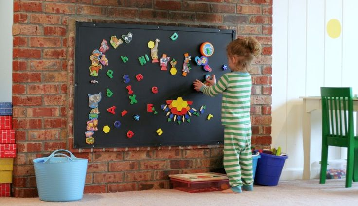 Designing Playspaces: Our Playroom from Fun at Home with Kids - putting a magnetic board like this over the fireplace in the family room would make loads of sense for our family needs right now