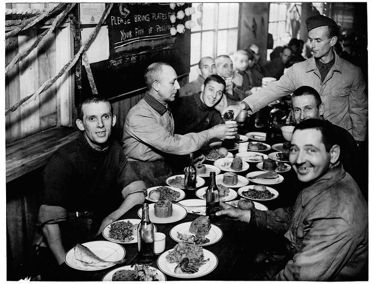 Christmas holiday party at the POW camp in Fukuoka jurisdiction, Japan, 1944 / 福岡管轄区内・豪華な食事に笑顔の捕虜。後ろの黒板には PLEASE BRING PLATES FOR YOUR FISH IF POSSIBLEと書かれている。 #prisoner-of-war #pow #camp #ww2 #japan