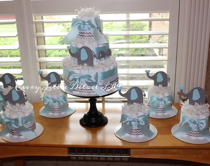 Elephant Theme Diaper Cake! This cake is blue, gray chevron and white, accented with 3 elephants made out of high quality cardstock! The perfect addition to any baby shower!  Made with 60-65 pampers swaddlers size 1 Measures approximately 9 inches wide and 12 inches tall All of my diaper cakes are made in a clean, smoke free environment The pampers are 100% usable!  Color change available, convo me with your request  Thanks for stopping by