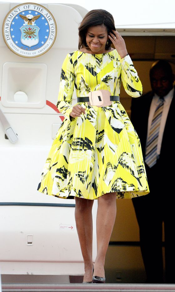 First Lady Michelle Obama wearing a belted yellow Kenzo dress during her tour of Asia