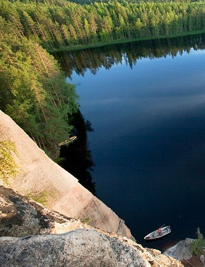 Repovesi National Park - #climbers were making their way up the near-perpendicular rock face, 50 metres above the #lake surface. It must be an amazing feeling! | #travel #vacation