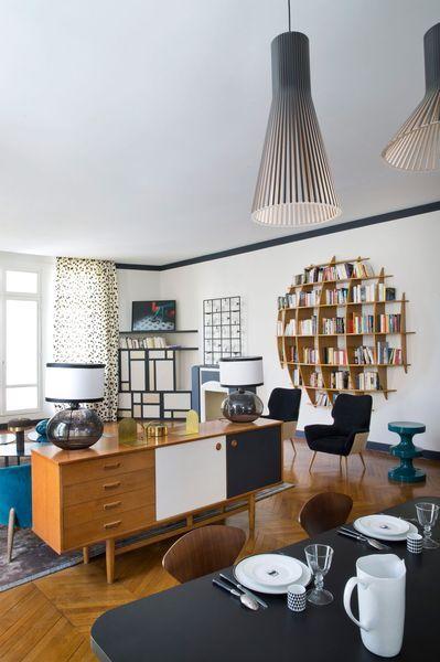 À voir: La salle à manger séparée du salon par une commode ultra déco mais que dire de la bibliothèque au mur !