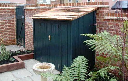 Outside painted lean-to storage with shingle roof.