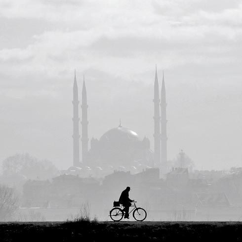 Uygar Korca - Bicyclist with sultan Selim Mosque in background, Edirne, Turkey.