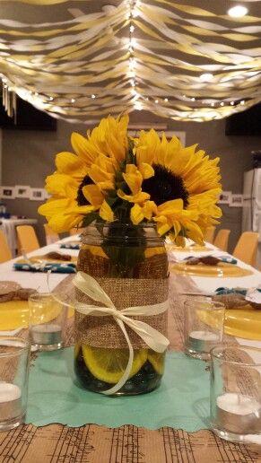 Simple sunflower centerpieces...mason jar, burlap ribbon, lemon slices, glass marbels, yellow food dye in water....