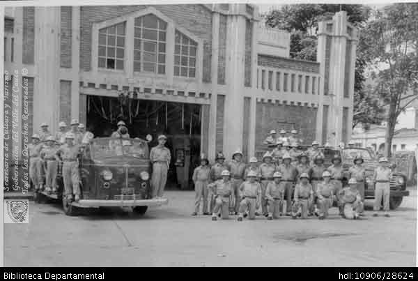 ◦El cuerpo de bomberos posando para una foto de recuerdo, en la antigua estación central, se aprecia a la izquierda la máquina America Lefrance Cali. C.1934. Biblioteca Departamental Jorge Garces Borrero y CBV