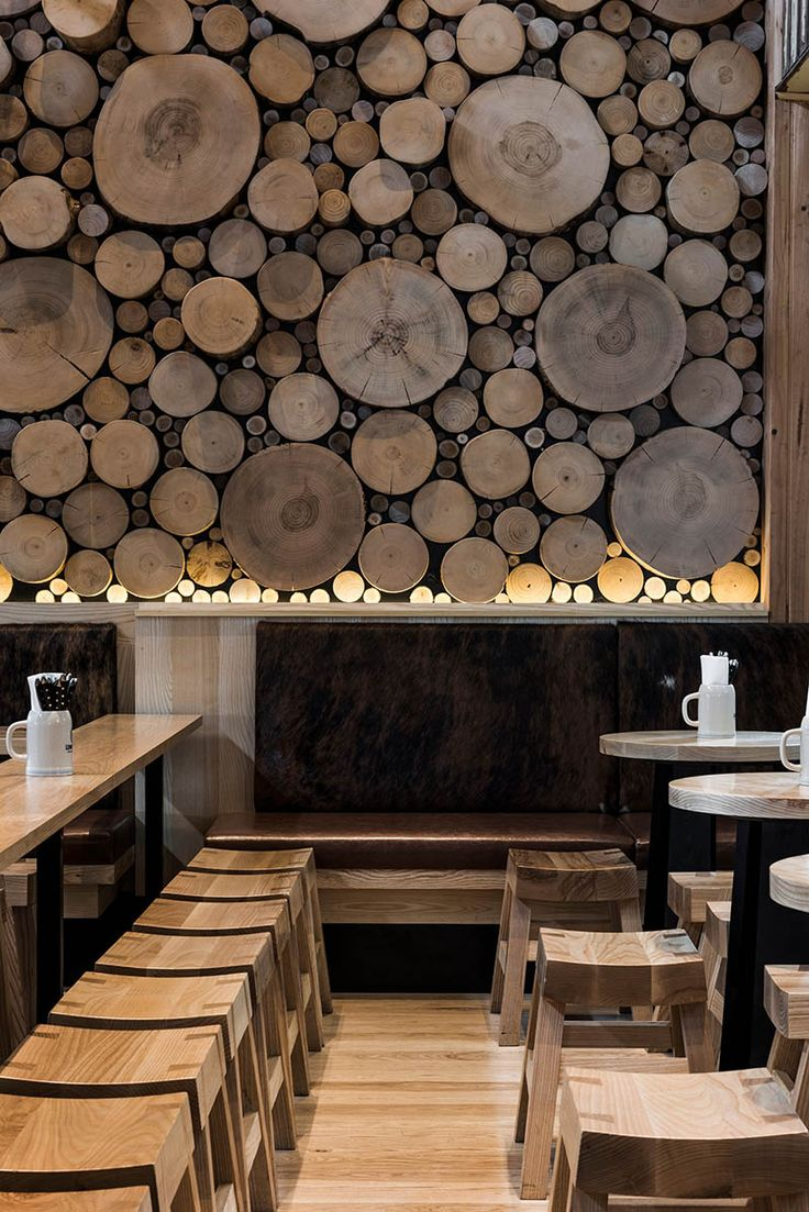 A giant log wall is a focal point in this restaurant in australia designed by techne architecture interior design