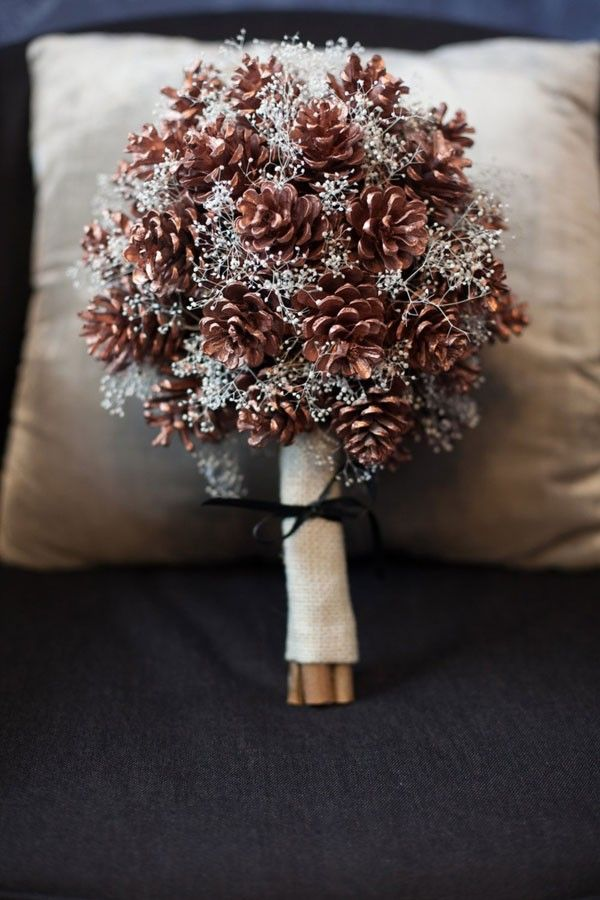 This combo of pine cones and glitter-sprayed baby's breath makes a stunning, wintry bridal bouquet. | See more seasonal symbols for winter weddings here: http://www.mywedding.com/articles/winter-wedding-ideas-pick-a-seasonal-symbol/