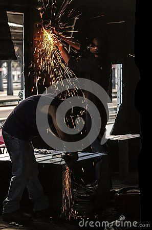 Workers cutting steel with angle grinder and sparks jumping all over the place. Repairing in train station an old wagon.