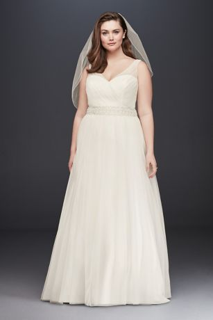 Simple and elegant, this timeless tulle A-line plus-size dress features a flattering V-neck bodice with illusion tank straps and a sparkling beaded waistband. The full, feather-light skirt gives the s