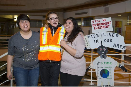 While passing through Toronto at York University, Rachel Thevenard, 22, in safety vest, hugs her road team, sisters Lindsay Gray, left, who is in charge of social media and Vanessa Gray, who manages water, vitamins and electrolytes for Thevenard. Thevenard is running the length of the Line 9 pipeline from Sarnia to Montreal.