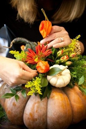 DIY fall-themed centerpiece with pumpkins and flowers