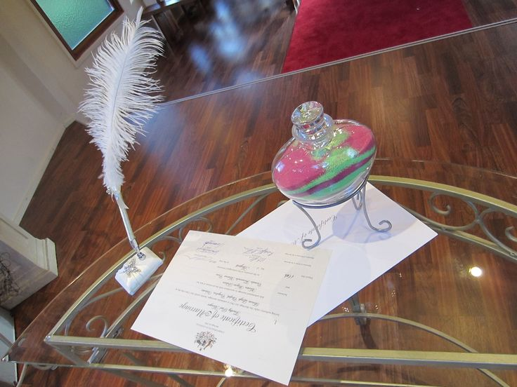 A love-heart shaped Sand Ceremony Vase sits on a Marriage Certificate at Bram Leigh chapel