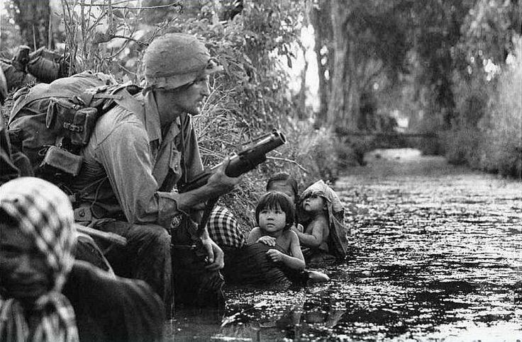 U.S. soldier and Vietnamese civilians take cover in a canal. The soldier is armed with an M79 grenade launcher.