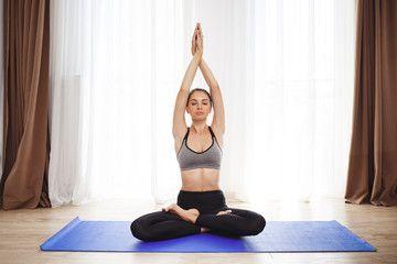 Beautiful young girl make yoga execises on floor