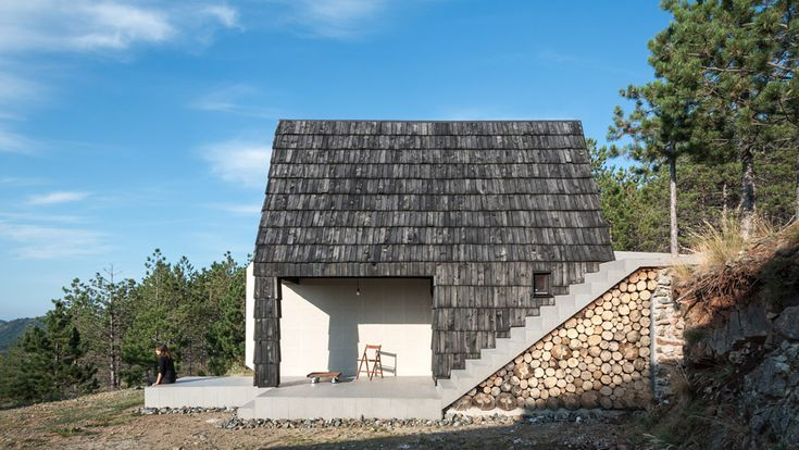 One half of this tiny mountain dwelling by Serbian practice EXE Studio is faced in white ceramic tiles, while the other is clad in dark timber shingles
