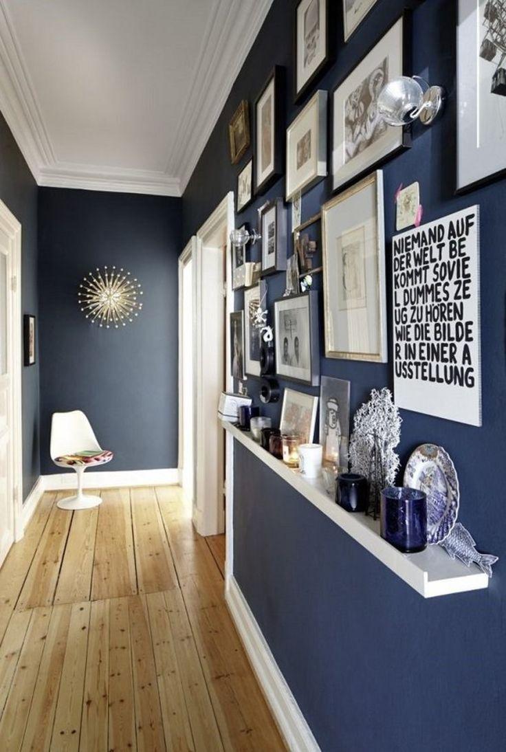 Przedpokój z granatowymi ścianami i drewnianymi panelami na podłodze - obrazki na ścianie