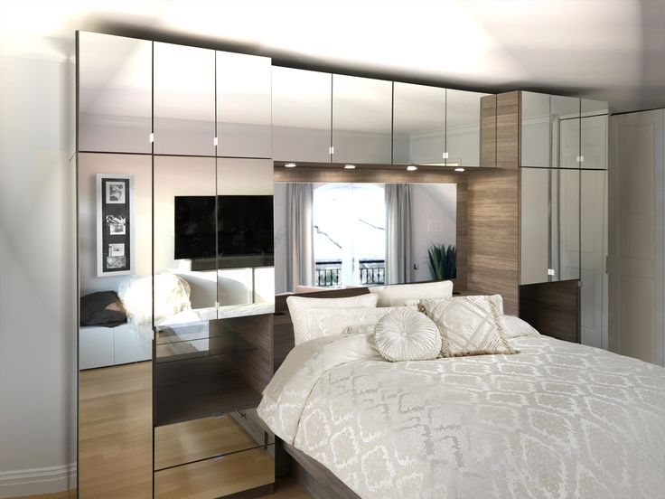 This wall is designed to take up only as much space as a headboard &2 nightstands, yet creating much more space for storage in your bedroom. Narrow wardrobe closets at left and right feature fully adjustable shelving. Storage bridge is a 4 door addition to give you a new place to store extra items in an area that is normally unused space in the bedroom. Mirrored headboard adds brightness and style to the bedroom. #storagebed #mirrored #furniture #closetbed #bedcloset #wallunit #modern…