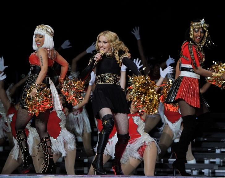 """It doesn't get much bigger than Madonna! More than 100 million viewers tuned in to watch the Material Girl amp up the crowd with performances of old classics like """"Like A Prayer,"""" as well as her new hit """"Give Me All Your Luvin."""" Madge was joined on stage by a blond Nicki Minaj and British singer M.I.A., who added a dose of controversy to the show after flipping the bird during the live performance."""