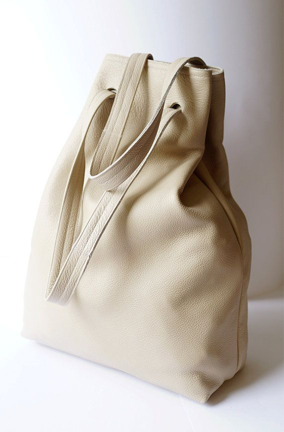 An extra large minimalistic shoulder bag. It has also the function of the backpack. Made of creamy thick leather. No lining. Dimesions: height: 49 cm/ 19,2 witdht: 36 cm/ 14,2 bottom-depth : 13 cm/ 5,2 straps : 64 cm/ 25,2 For these bag, please expect 2 weeks for your item to be made and prepared for shipment!  Standard delivery time:  European union: 4 - 10 days  Europe (not EU): 7 - 14 days  U.S.A., Canada: 10 - 20 days  Australia, South America, Asia, India, North Africa: 1 - 3 weeks  We…
