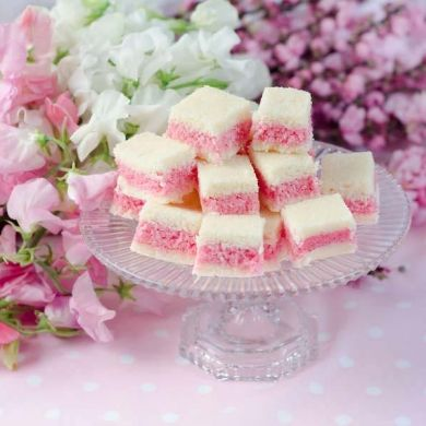 Rosey Coconut Ice* 450g desiccated coconut,2 c icing sugar,200ml evaporated milk,50g butter,1/2 tsp salt,1/2 tsp rose essence,3-4 drops red food color*In microwave on high 2-3 mins,put coconut ,sugar,milk,butter & salt.Remove & stir ,add flavoring.Divide mixture,add color.Spoon white mixture on bottom,top w/ pink.Then add rest of white.Level & press.Refrigerate 4 hrs before cutting.