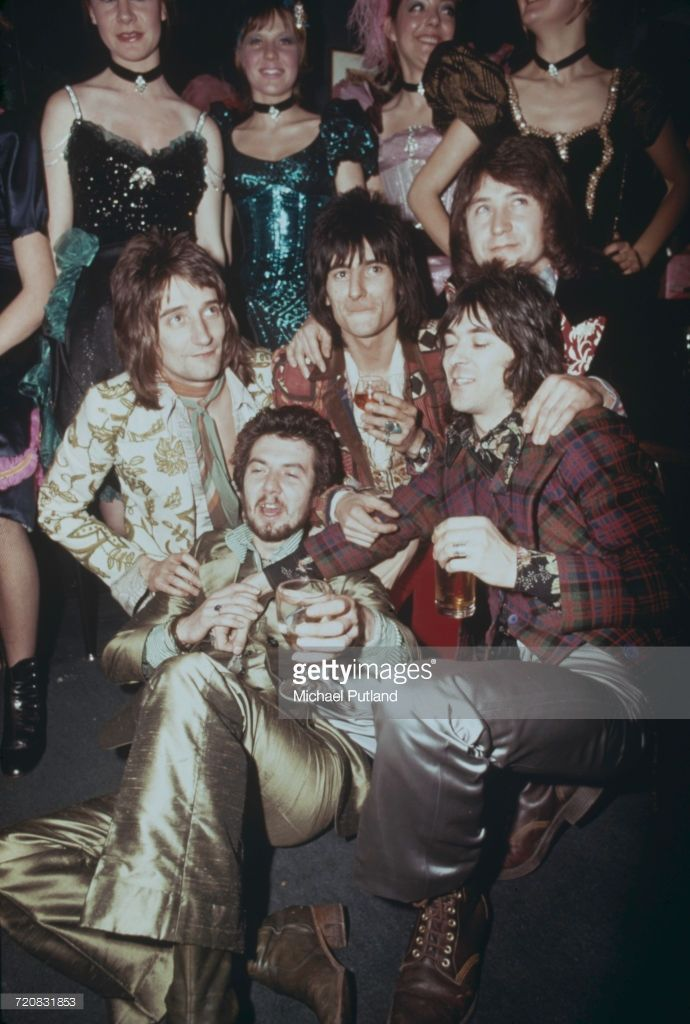 English rock group Faces with a group of showgirls at a reception at the Tramp nightclub in London for the release of their album 'Ooh La La', 5th April 1973. The band are (clockwise from lower left) bassist Ronnie Lane (1946 - 1997), singer Rod Stewart, guitarist Ronnie Wood, drummer Kenney Jones and keyboard player Ian McLagan.