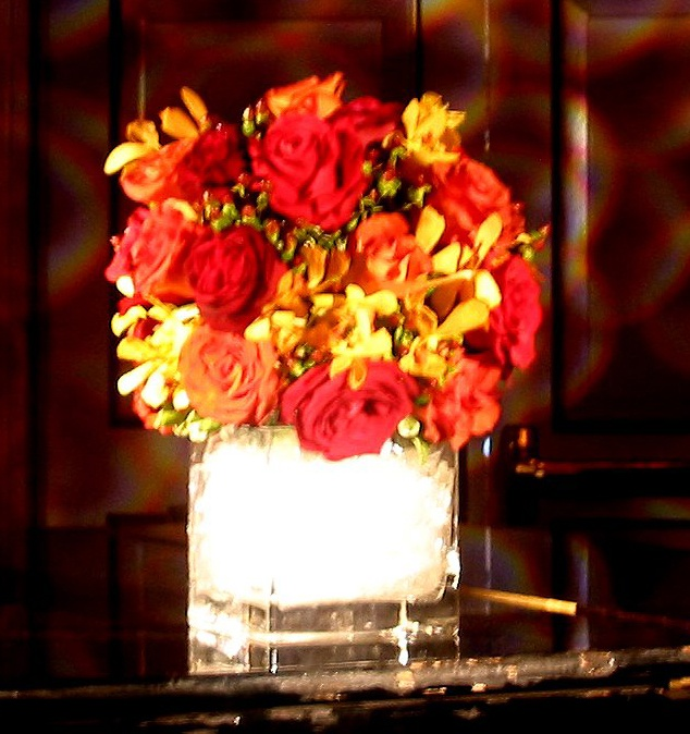 This is a cube vase floral arrangement that features roses, mokara orchids and hypericum in a red, orange and yellow color scheme.