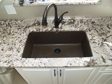 Bianco Antico Granite with Touch Delta faucets & Blanco Silgranit u/m sinks. Espresso Cabinets in the island & white cabinets on the perimeter.