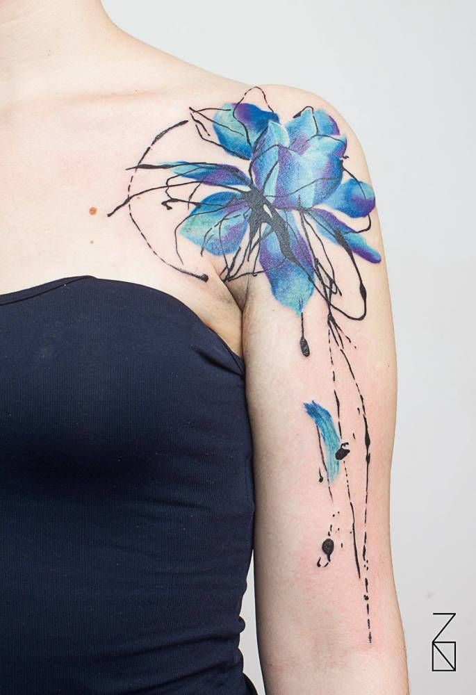 Abstract style blue lotus flower tattoo on the left shoulder.