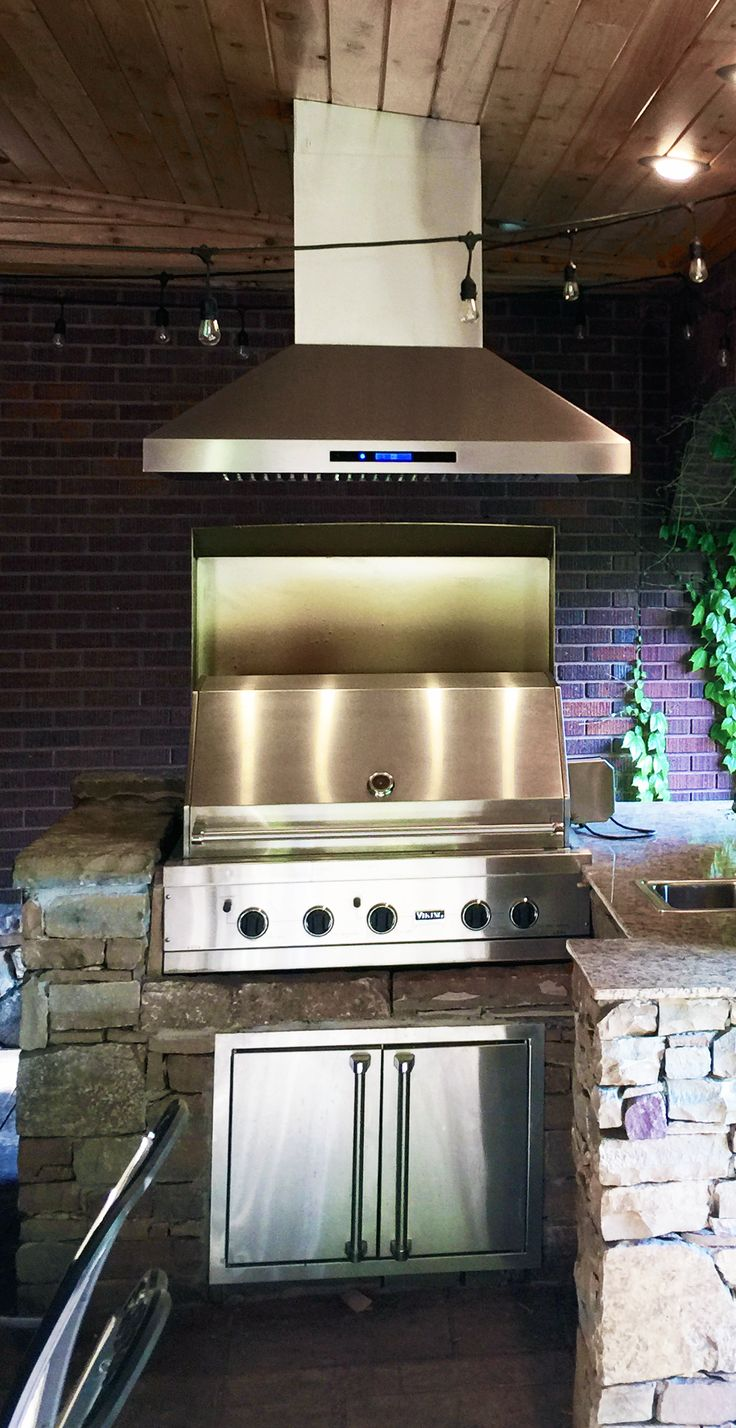outdoor kitchen featuring the powerful and beautiful stainless steel pros island range hood from proline range
