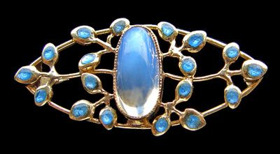 JESSIE M. KING 1873-1949 (Scottish) Liberty & Co Brooch  Gold, moonstone & enamel Length: 1.4 cm (0.5 in)  Width: 3.1 cm (1.2 in)  Marks: 15 ct  Fitted case  Literature: cf. Liberty Jewellery sketch-book, page 27 Model number: 1800
