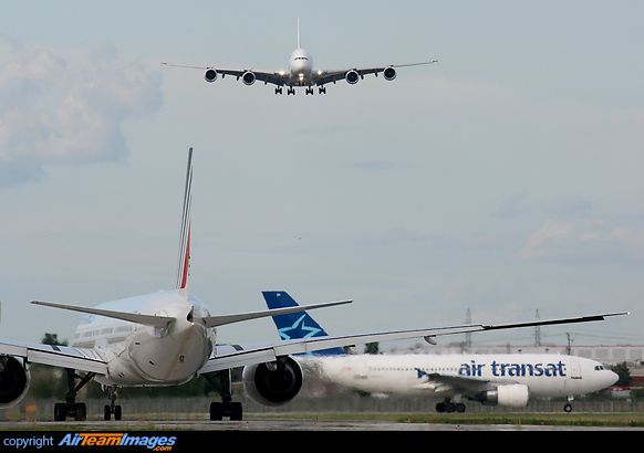 Air France A380 on final while Air Transat A310 is holding short and Air France B777 taxies for departure.