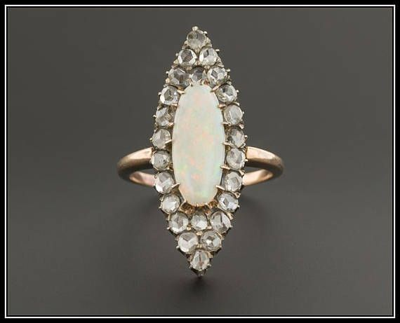 A stunning 10k gold antique opal & diamond ring!!! Opal, the birthstone of October, has the ability to delight all those who gaze upon it with its rainbow flashes of color. This ring (circa 1890-1910) features a white oval opal cabochon with flashes of orangey peach and green