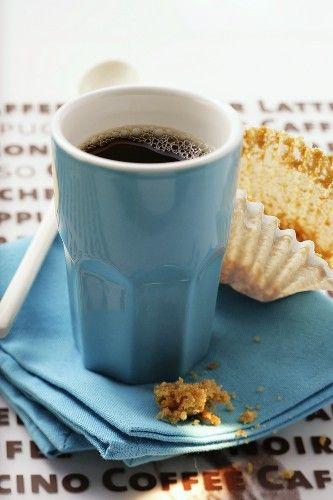 Blaue Espressotasse und leeres Muffin-Papierförmchen