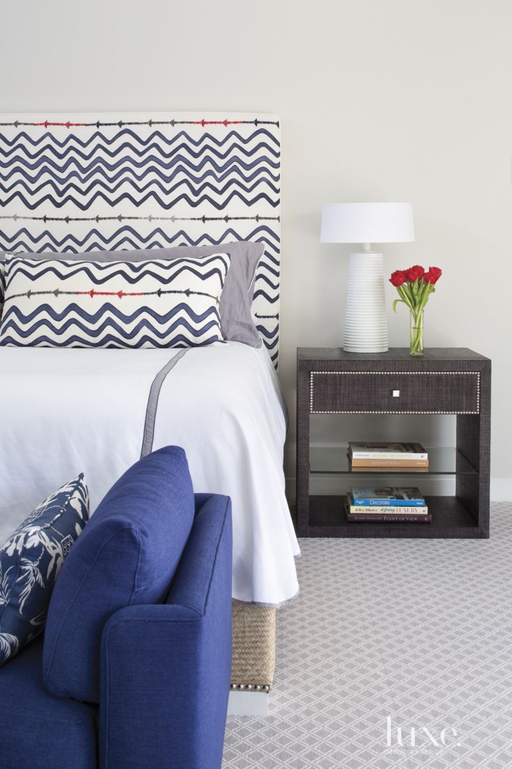 The master's custom bed has a nailhead-trimmed raffia box spring and a headboard upholstered in Christopher Farr Cloth's indigo Rick Rack from John Rosselli & Associates.