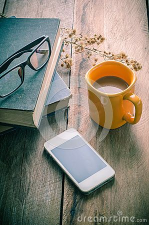 Yellow coffee cup placed on a wooden table with a smart phone, glasses, books, dried flowers - tone vintage.