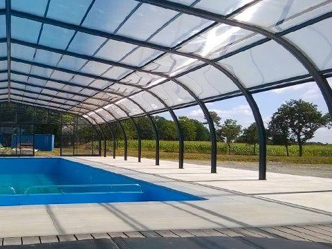 """Abri haut de piscine posé au parc résidentiel de loisirs """"Le domaine du Téno"""" à Marzan."""