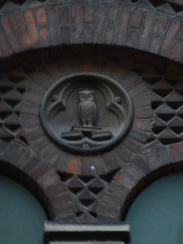 Uglerelief på den gamle katolske pigeskole i Ryesgade. Uglen er symbol på visdom og attribut for gudinden Athena der var beskytter af kunst og videnskab.