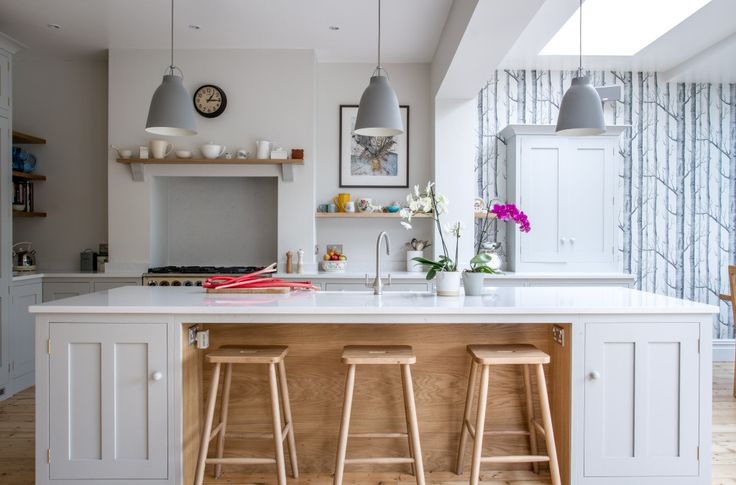 Shaker style oak kitchen painted in Farrow & Ball Pavilion Gray with Bianco Venato engineered quartz worktop. The island has a built in breakfast bar with beech stools. The three Caravaggio steel hanging pendant lights adds a subtle touch of colour. Floating oak shelves and oak mantelpiece display beautiful ceramics.