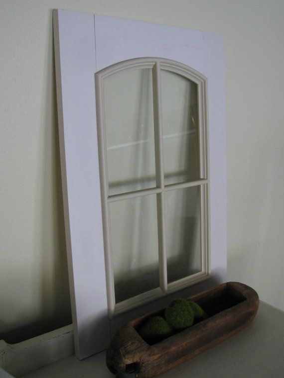 This is a shabby off white wood grained arch window wall hanging This can be hung from the wall, propped up against the wall.Off white distressed paint some holes on back side Arch divided frame over glass  panel Measures 21.75 H x15 W hardware not included. Maybe something like this to cover electrical box.