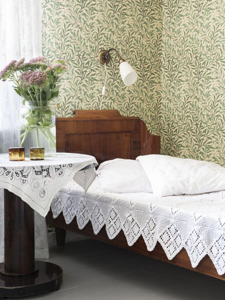 """""""Vi målade taken här nere för att få en lite ljusare känsla i rummen. Vi renoverade även skorstenarna så att det nu går att elda i alla kakelugnar"""", säger Marie. Gästrummet med sin ljuvliga grönmönstrade tapet. Den gamla sängen ingick i husköpet. Virkat sängöverkast, som fyndats på loppis, gör sig bra till."""