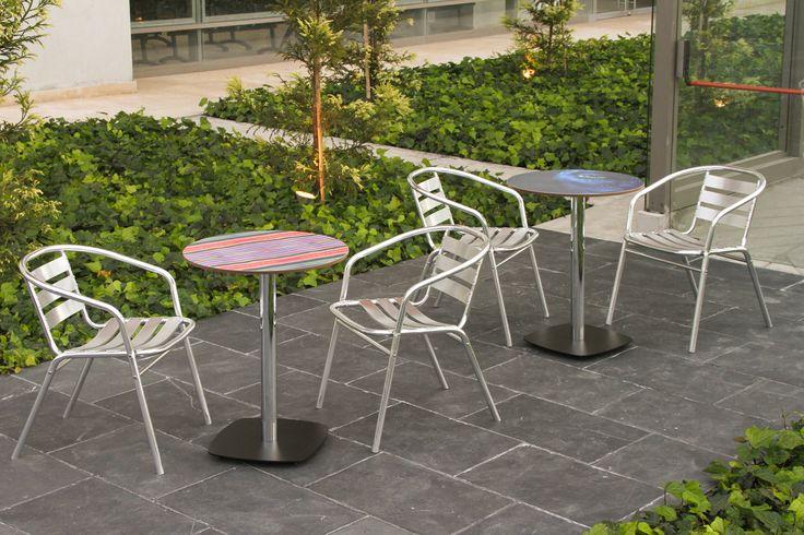Utilización de nuestras mesas tipo pedestal para terraza. Bases ARK pintadas en negro con columna redonda cromada y tableros con decorado personalizado.