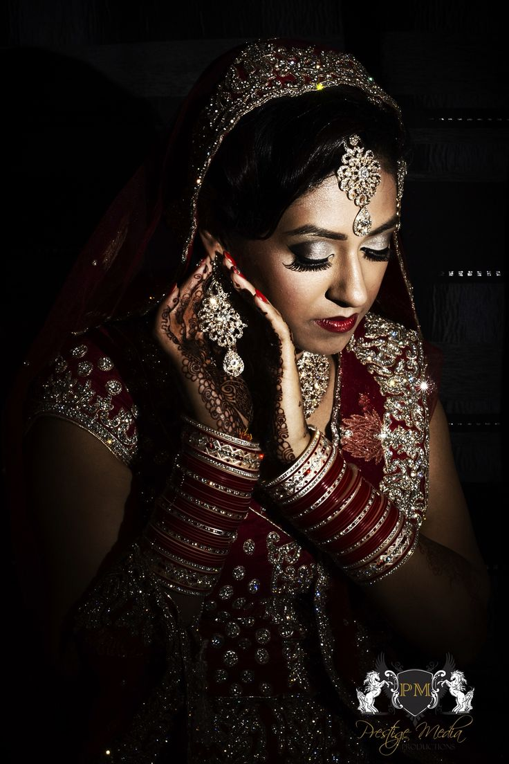 Bride posing with earring whilst getting ready for her Indian Sikh wedding
