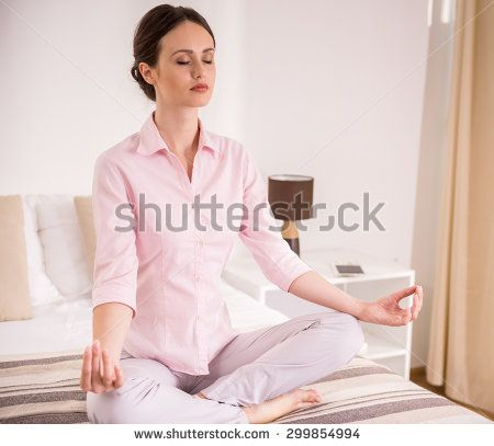 Woman sitting on bed and meditating in lotus pose at the hotel room.