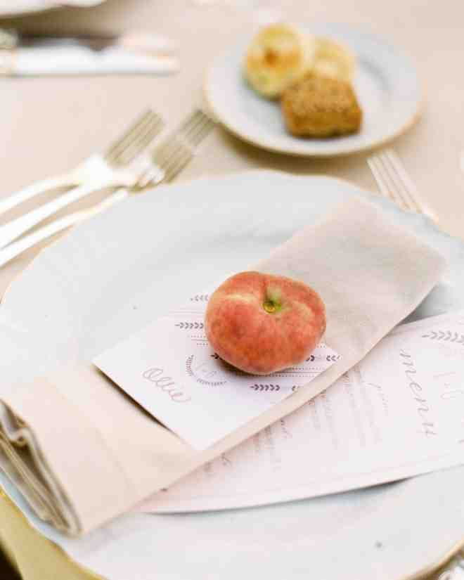 Wedding Paper Divas created dinner menus and name cards for all the guests. Each name card was weighted with a small peach to keep it from blowing away.