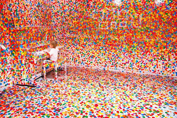 Child seated at piano in room covered in stickers.  From an interactive exhibit at the Gallery of Modern Art in Brisbane.