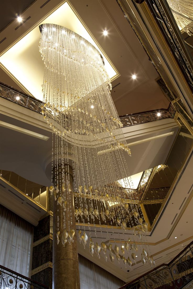 The staircase area in Lotte Hotel Moscow winds its way around in a 12-meter optical fiber lit waterfall made of cut crystal and smooth frosted beads combined with hand-blown glass leaves. #light #lighting #design #designlighting #interior #interiortrends #crystal #bohemiancrystal #chandelier #hospitality #hotel #staircaselighting #lightinginspirations #lightingtips #preciosa #preciosalighting #preciosainspirations