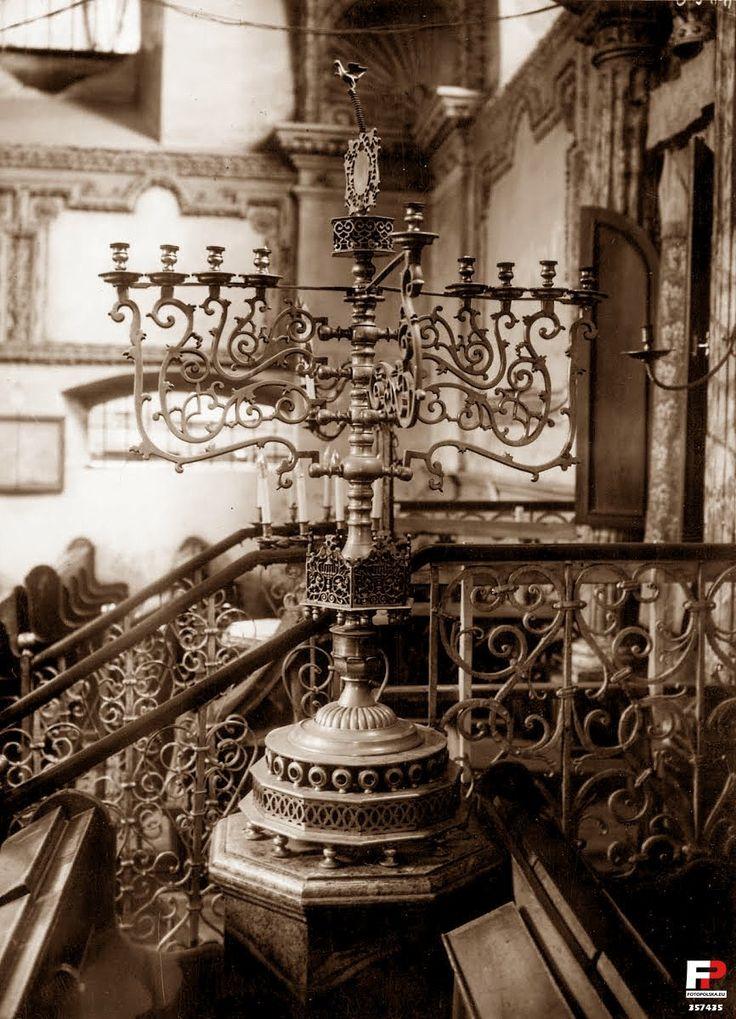 Lata 1925-1930 , Wnętrze zamojskiej synagogi - dziewięcioramienny świecznik żydowski zapalany podczas święta Chanuka. Chanuka trwa przez 8 dni, w czasie których zapala się kolejne świeczki – po jednej na każdy dzień. Jedna ze świec – Szamasz – jest świecą dodatkową, dziewiątą, którą zapala się pozostałe. Szamasz powinien być trochę oddalony od pozostałych świeczek lub znajdować się nieco powyżej nich.Synagoga, Zamość - 1928 rok