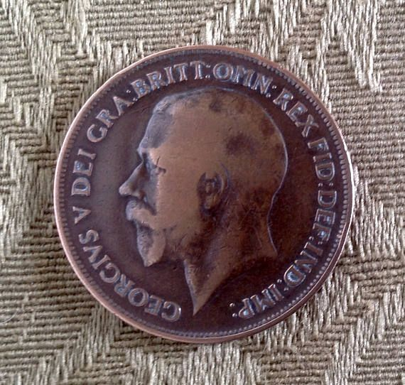 A 1919 British One Penny Coin...produced by the Heaton Mint in the reign of George V. Coin ,erasures 1.2 across, and has Britannia , ONE PENNY and 1919 on one side, The reverse side shows the head of George V, with Latin inscription around the edge. In nice condition, with all detail clearly visible.