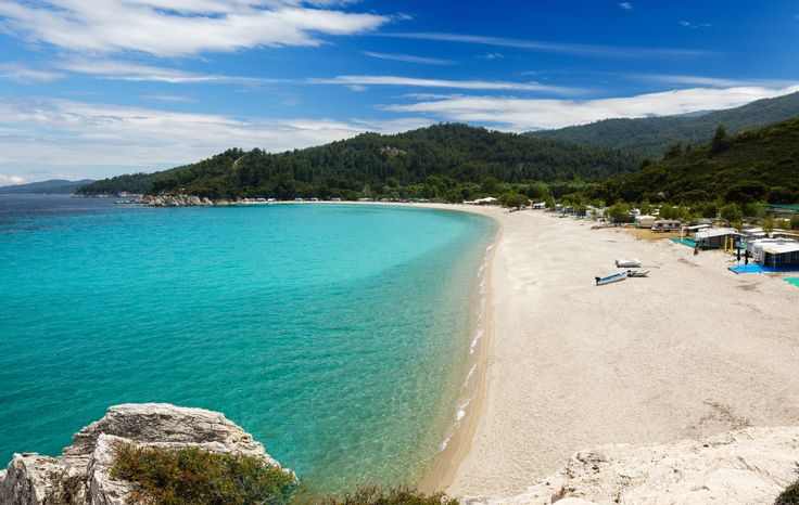 Armenistis beach invites you to swim at its crystal clear blue waters with white, thin sand, full of plane and elm trees
